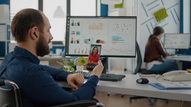 Homme invalide handicapé et paralysé tenant un smartphone parlant sur webcam avec un collègue lors d'une vidéoconférence, d'un appel vidéo, d'une réunion en ligne avec un partenaire commercial assis en fauteuil roulant dans un bureau de démarrage
