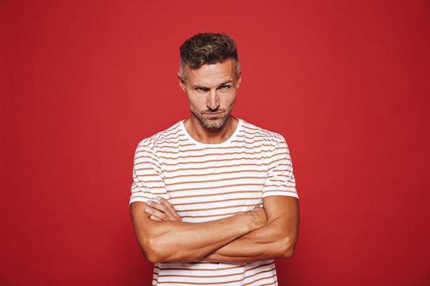 Homme irrité des années 30 en t-shirt rayé debout avec les bras croisés et regard en colère isolé sur rouge