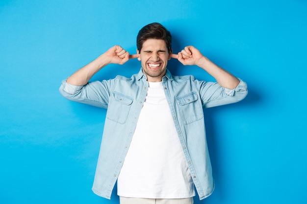 Homme irrité fermer les oreilles des voisins bruyants, à la dérangé en se tenant debout contre le mur bleu