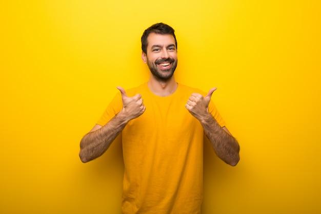 Homme, isolé, jaune, vibrant, couleur, donner, a, pouces haut, geste, à, mains, et, sourire