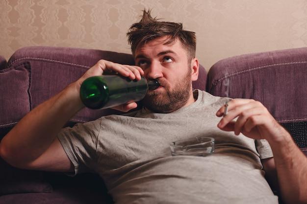 L'homme ivre boit de l'alcool.