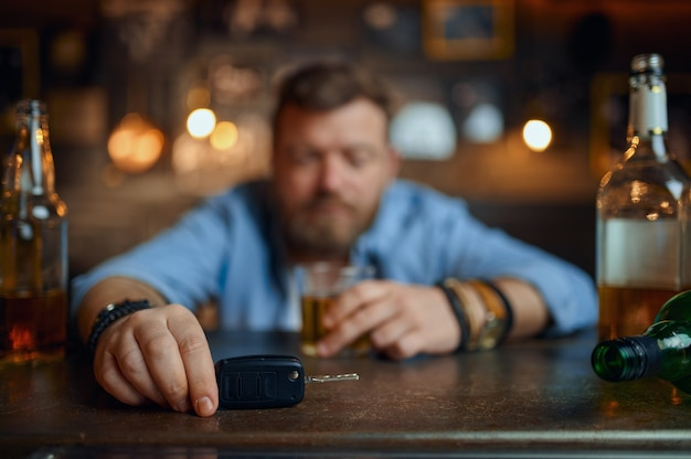 Homme ivre avec clé de voiture assis au comptoir en bar