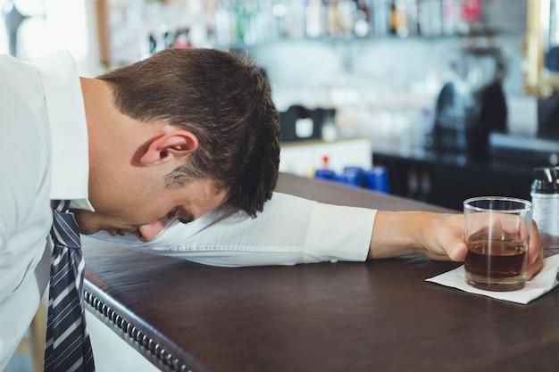 Homme ivre dormant sur un comptoir de bar
