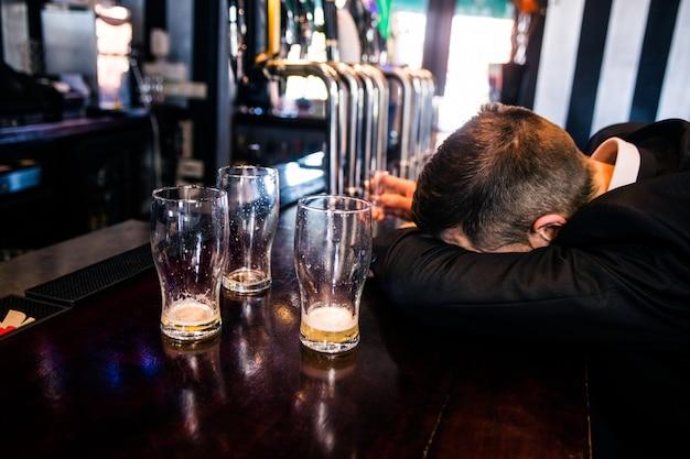 Homme ivre avec des lunettes vides dans un bar