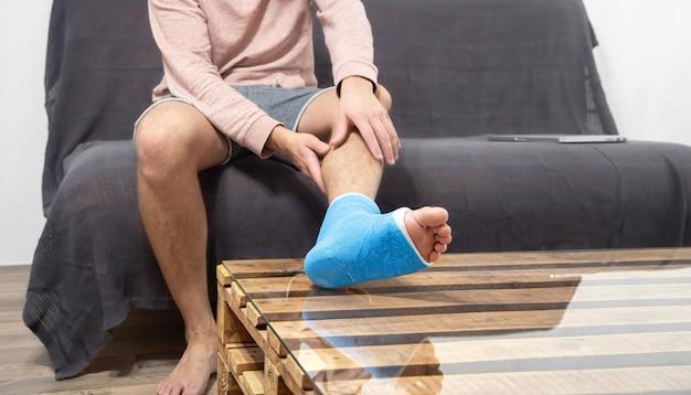 Homme avec une jambe cassée en plâtre sur le canapé. le talon ou le pied ont des os cassés avec un mur plâtré et médical.