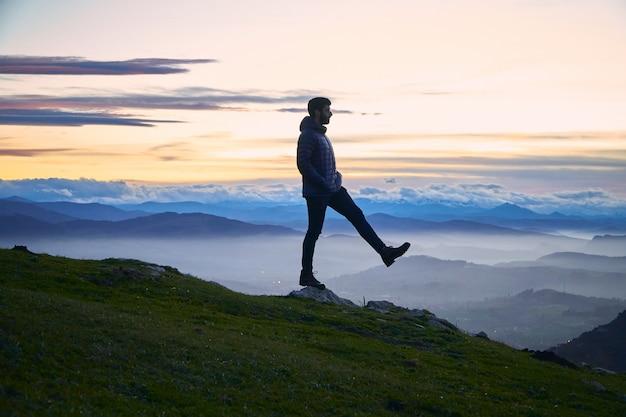 Un homme avec une jambe levée au sommet d'un rocher sur une colline avec des montagnes en arrière-plan