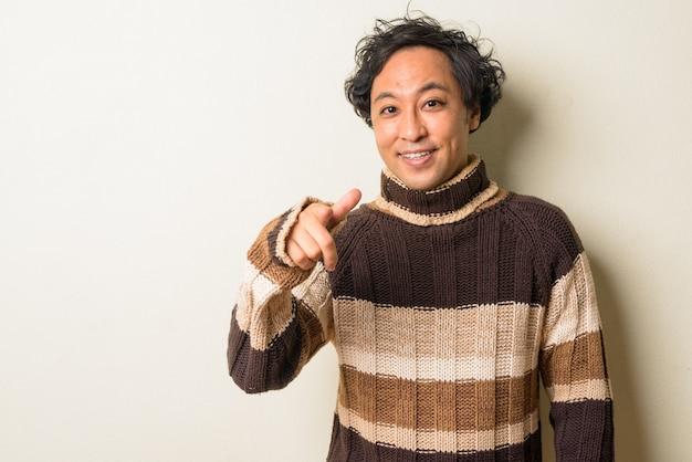 Homme japonais aux cheveux bouclés prêt pour l'hiver à l'intérieur