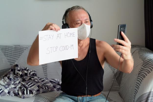 Homme japonais mature avec masque appel vidéo et montrant rester à la maison signe sous quarantaine