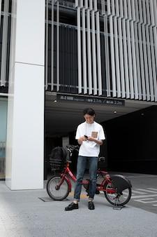 Homme japonais avec son vélo à l'extérieur