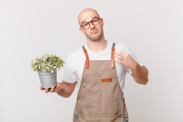 Homme de jardinier à l'air arrogant, réussi, positif et fier, pointant vers lui-même