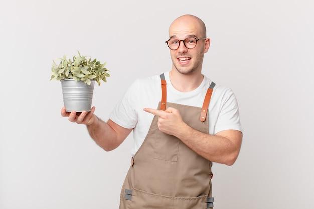Homme jardinier à l'air excité et surpris pointant vers le côté et vers le haut pour copier l'espace