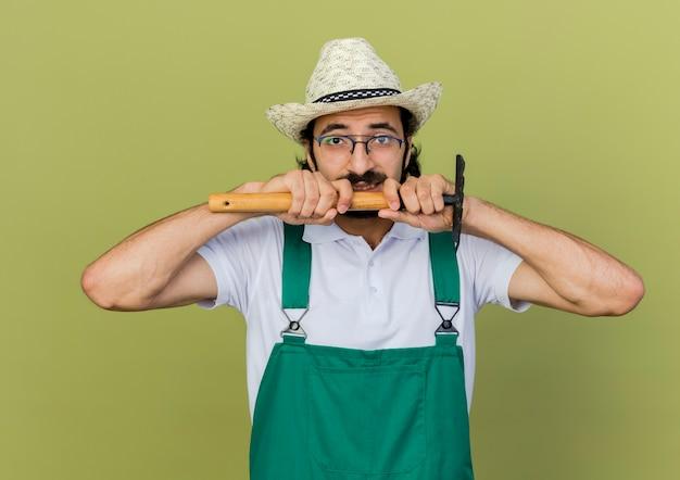Homme jardinier anxieux dans des lunettes optiques portant chapeau de jardinage détient râteau à la recherche