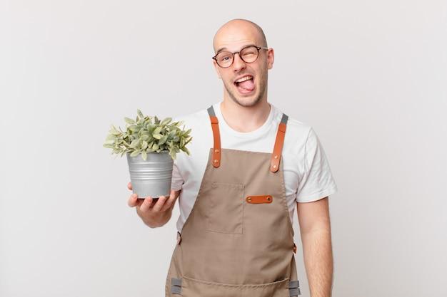 Homme de jardinier avec une attitude joyeuse, insouciante et rebelle, plaisantant et tirant la langue, s'amusant