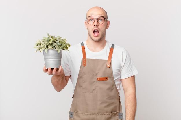 Homme de jardinier ayant l'air très choqué ou surpris, regardant la bouche ouverte en disant wow