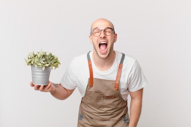 Homme jardinier criant agressivement, l'air très en colère, frustré, indigné ou agacé, criant non