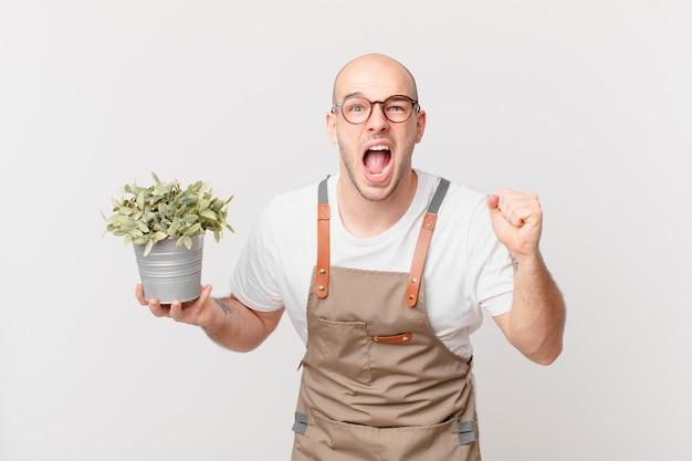 Homme de jardinier criant agressivement avec une expression fâchée ou avec des poings serrés célébrant le succès