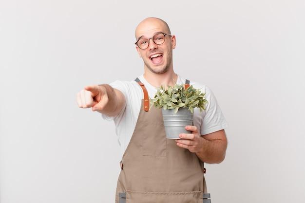 Homme de jardinier pointant vers la caméra avec un sourire satisfait, confiant et amical, vous choisissant