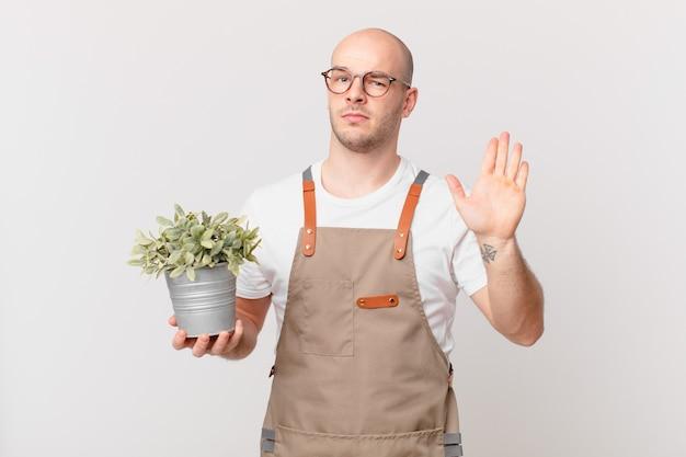 Homme de jardinier à la recherche de sérieux, sévère, mécontent et en colère montrant la paume ouverte faisant un geste d'arrêt