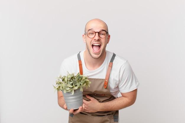 Homme jardinier riant aux éclats d'une blague hilarante, se sentant heureux et joyeux, s'amusant