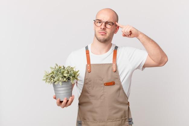 Homme de jardinier se sentant confus et perplexe, montrant que vous êtes fou, fou ou fou