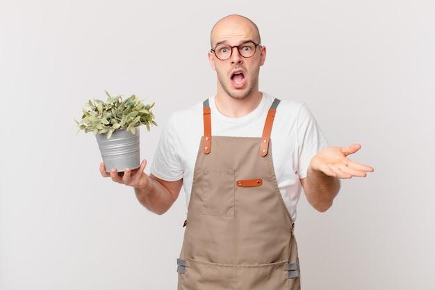 Homme jardinier se sentant extrêmement choqué et surpris, anxieux et paniqué, avec un regard stressé et horrifié