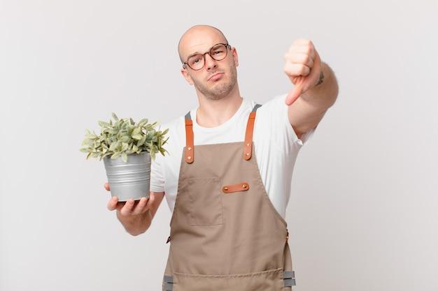 Homme de jardinier se sentant fâché, en colère, agacé, déçu ou mécontent, montrant les pouces vers le bas avec un regard sérieux