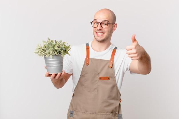 Homme de jardinier se sentant fier, insouciant, confiant et heureux, souriant positivement avec le pouce levé