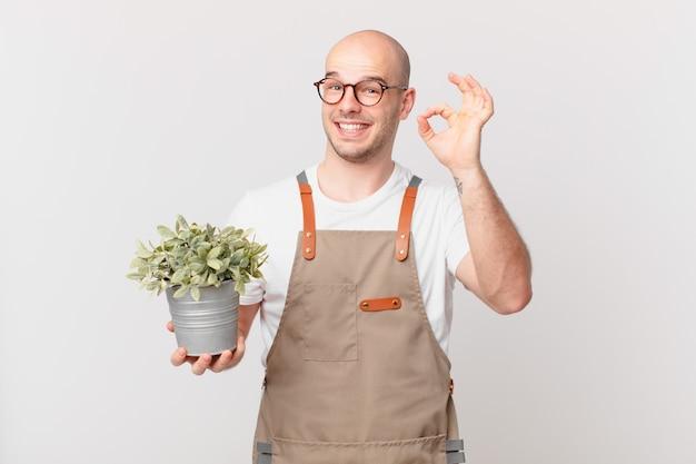 Homme de jardinier se sentant heureux, détendu et satisfait, montrant son approbation avec un geste correct, souriant