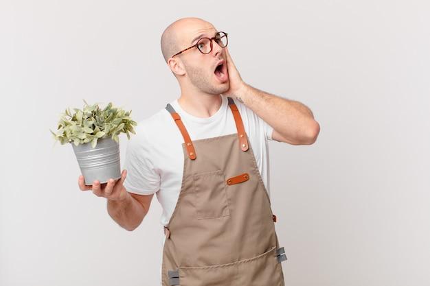 Homme de jardinier se sentant heureux, excité et surpris, regardant de côté avec les deux mains sur le visage