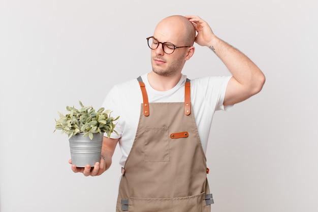 Homme de jardinier se sentant perplexe et confus, se grattant la tête et regardant sur le côté