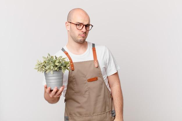 Homme de jardinier se sentant triste, contrarié ou en colère et regardant de côté avec une attitude négative, fronçant les sourcils en désaccord