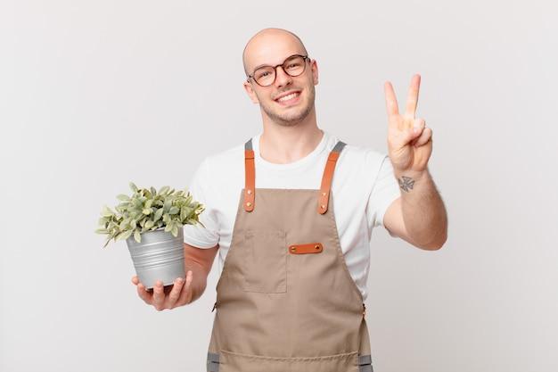Homme jardinier souriant et à l'air sympathique, montrant le numéro deux ou la seconde avec la main vers l'avant, compte à rebours