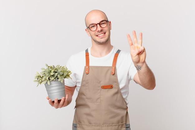 Homme jardinier souriant et à l'air sympathique, montrant le numéro trois ou troisième avec la main en avant, compte à rebours