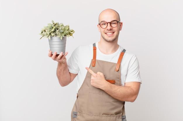 Homme jardinier souriant joyeusement, se sentant heureux et pointant vers le côté et vers le haut, montrant l'objet dans l'espace de copie