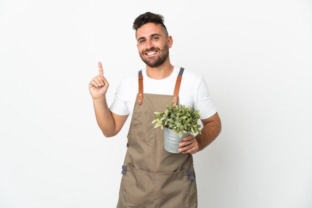 Homme jardinier tenant une plante sur fond blanc isolé montrant et levant un doigt en signe de la meilleure