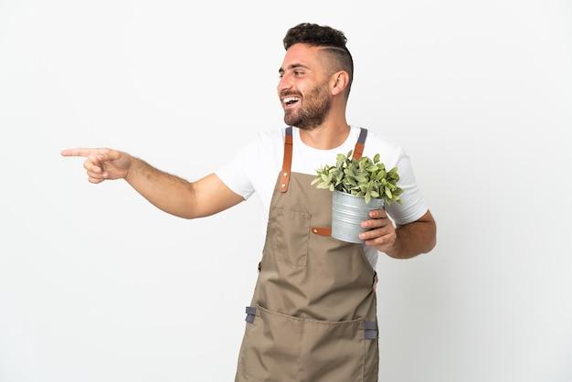 Homme jardinier tenant une plante sur fond blanc isolé, pointant le doigt sur le côté et présentant un produit
