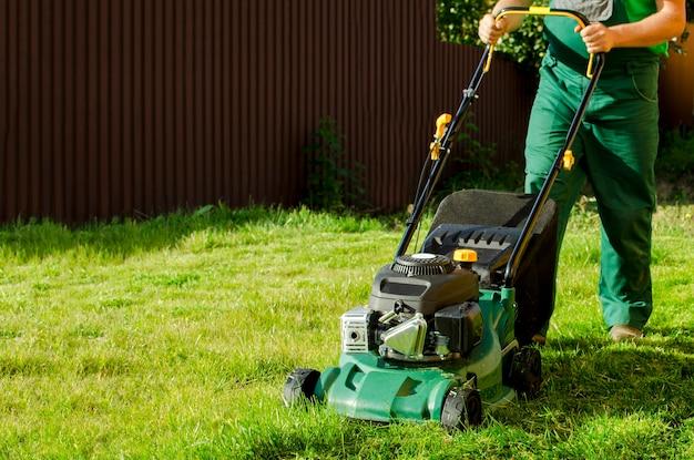 L'homme jardinier tondre la pelouse avec tondeuse poussée