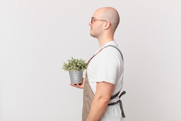 Homme jardinier sur la vue de profil cherchant à copier l'espace devant, à penser, à imaginer ou à rêvasser