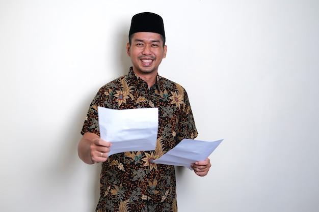 Homme javanais souriant amical tout en donnant un document papier