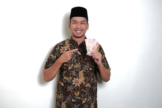 Homme javanais souriant heureux tout en pointant du doigt sur le papier-monnaie qu'il détient