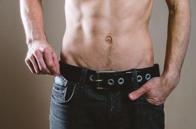Homme en jean noir sort un préservatif de sa poche avant