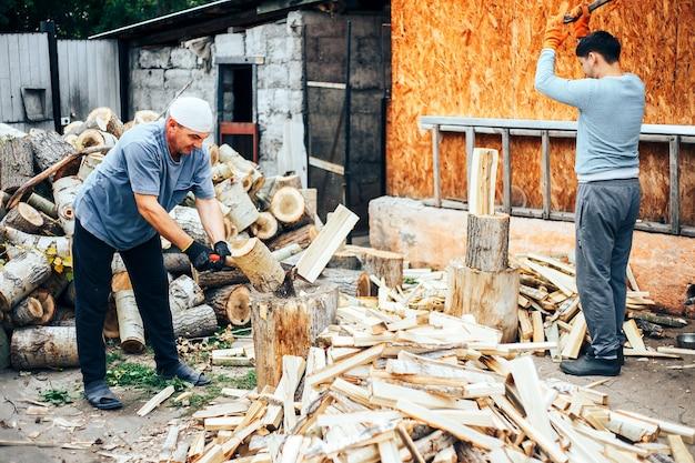 Homme en jeans et chemise à carreaux debout près de souche avec une hache dans les mains
