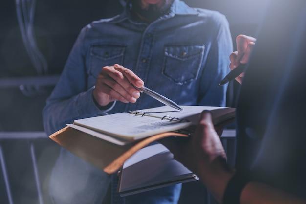 Homme en jeans donne des conseils sur le travail dans un cahier avec des collègues au bureau.