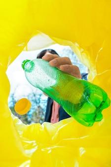 Homme jetant une bouteille en plastique verte dans une poubelle.