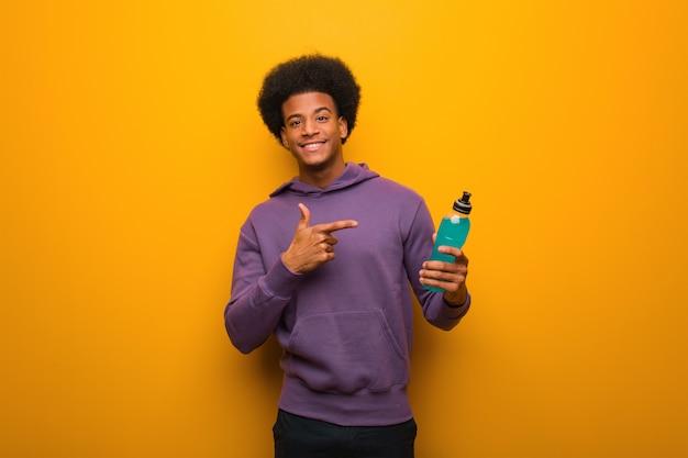 Homme jeune afro-américain de remise en forme tenant une boisson énergétique pointant vers le côté avec le doigt