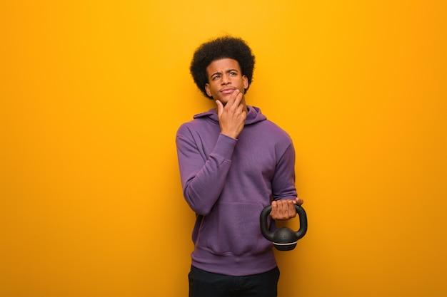 Homme jeune afro-américain de remise en forme, tenant un haltère doutant et confus