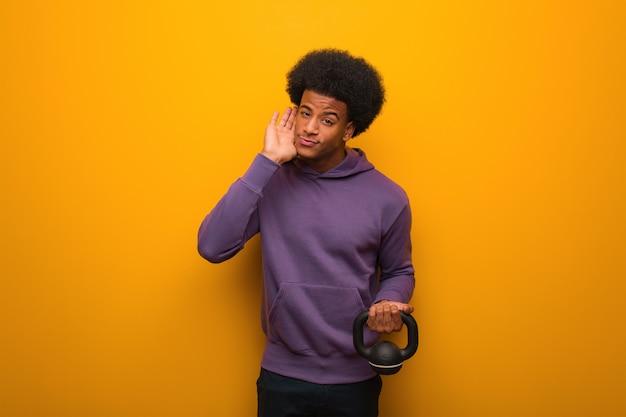 Homme jeune afro-américain de remise en forme tenant un haltère essayer d'écouter un potin