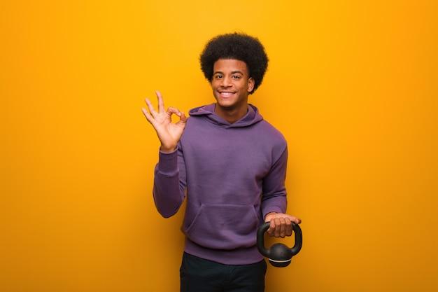 Homme jeune afro-américain de remise en forme tenant un haltère gai et confiant faisant geste ok
