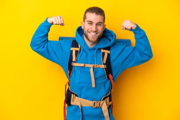 Homme jeune alpiniste caucasien avec un gros sac à dos isolé