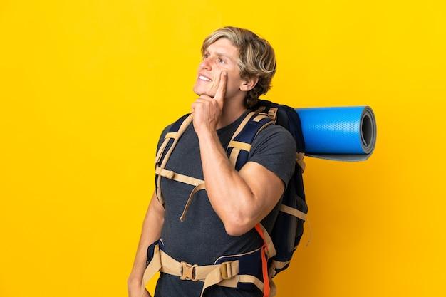 Homme jeune alpiniste sur fond jaune isolé pensant une idée tout en regardant
